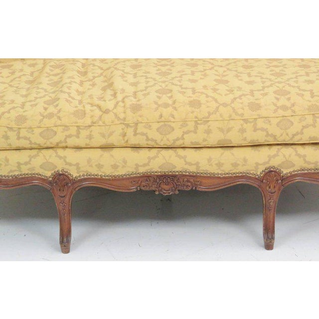 Carved walnut frame. Yellow decorative upholstery.