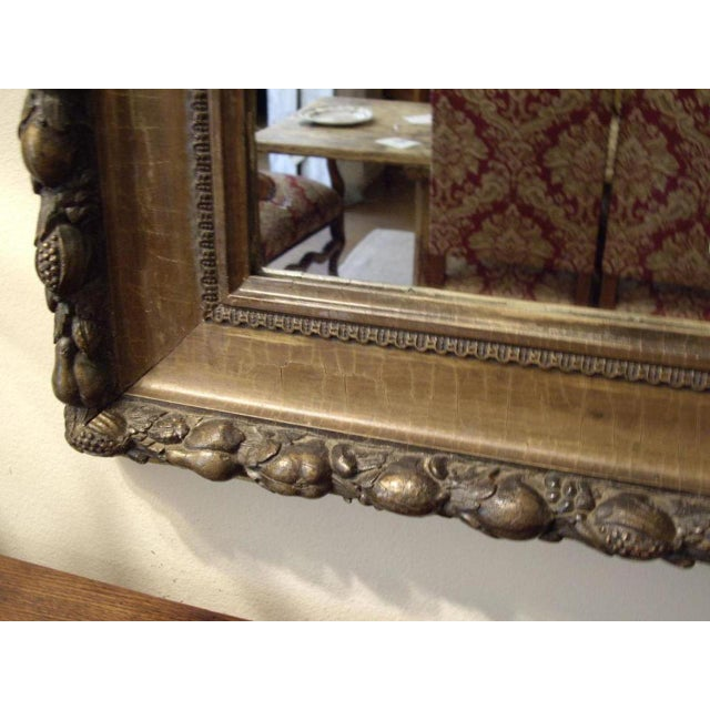 Italian mirror with fruit relief decoration. Worn gilt. Circa: 19th Century.