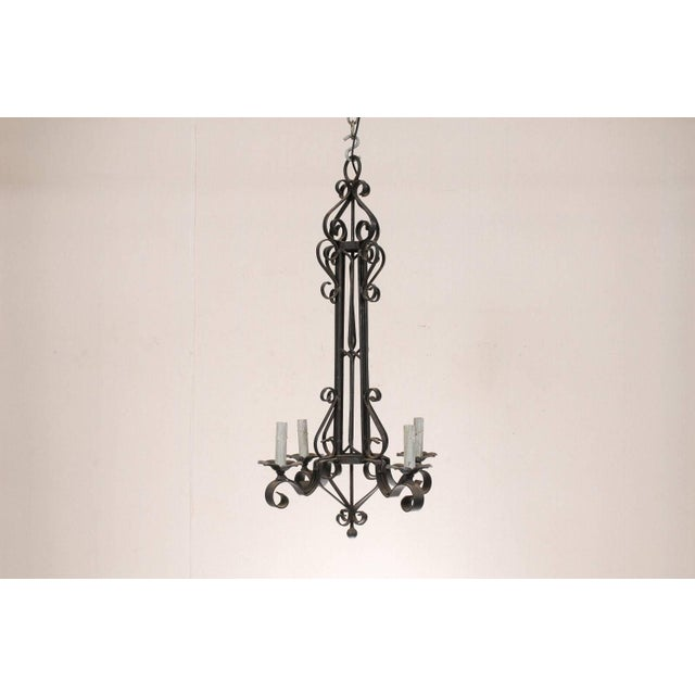 A French four-light iron chandelier. This French mid-20th century black iron chandelier features a linear column in its...