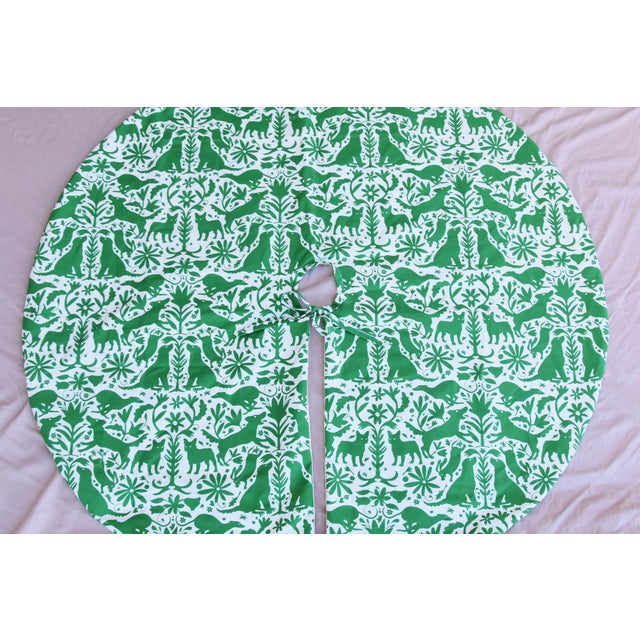 Custom-tailored Christmas tree skirt made from a printed cotton fabric depicting a green-and-white dog and floral Otomi...