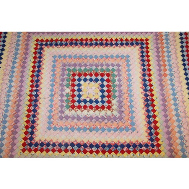 This finely pieced postage stamp trip around the world pattern quilt is in good condition and resembles Easter or spring...
