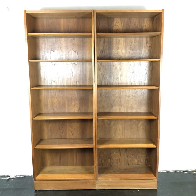 A pair of bookcase streamlined into a minimal, elegant form. Designed by Poul Hundevad. The bookcase teak that's patinated...