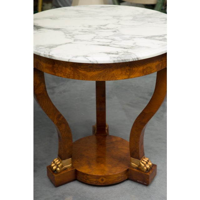 This beautifully proportioned burl walnut Empire style circular table has a white marble top over a deep frieze, supported...