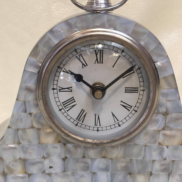 THis beauty is solid Aluminum with a Mother of Pearl mosaic face. The back has a lid that screws on for the batthery...