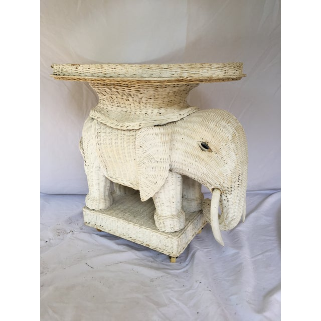 "Vintage white wicker elephant table with removable mirrored tray top and casters. Overall measures 25""l x 16""w x 23""h;..."