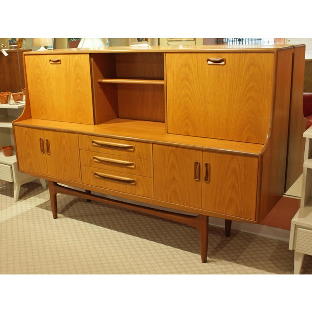 Mid-century modern credenza with bar and storage above double cabinets and 3 doors. Teak and teak veneers. Desirable fold...