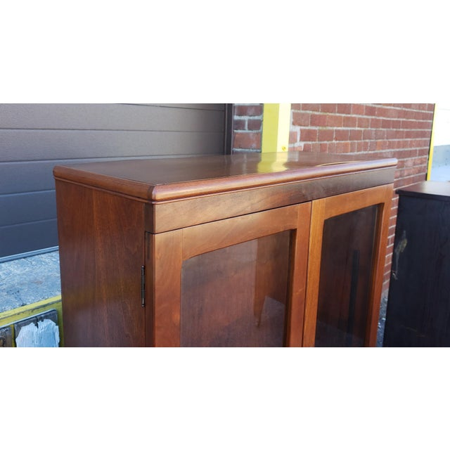 Walnut double glass door hallway bookcase cabinet, c1930s. Rectangular form with rounded edges over 2 glass front cabinet...
