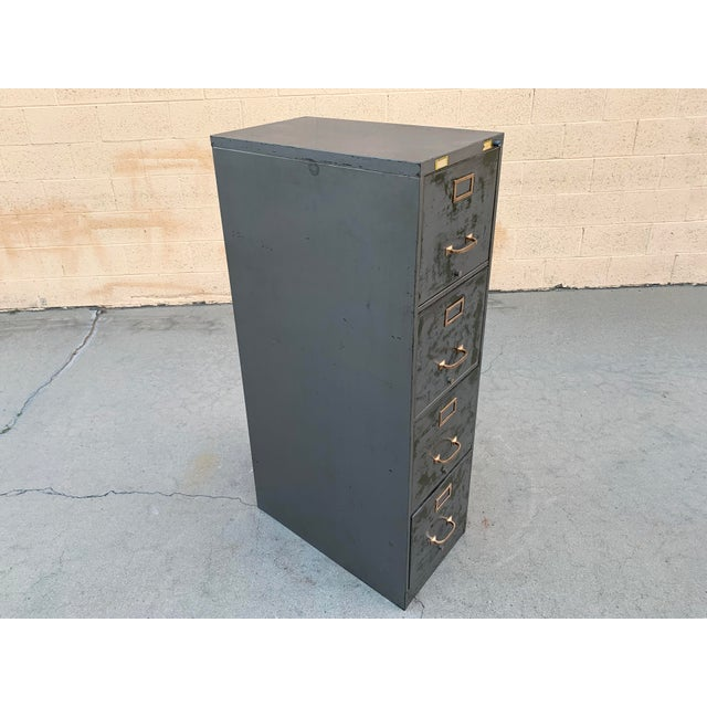 1940s steel file cabinet with a distressed finish and brass hardware polished to a shine. 4-drawer vertical configuration...
