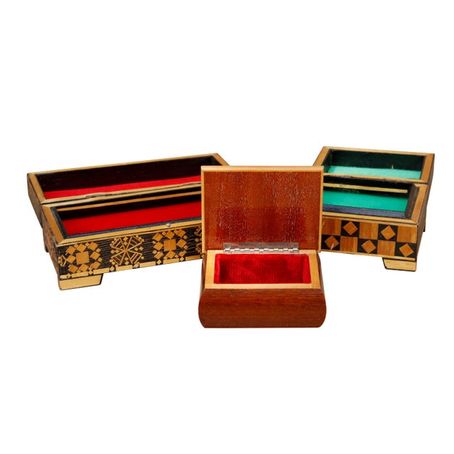 A set of three bohemian trinket boxes with red & green velvet interiors. Two are decorated with bamboo pieces laid in...