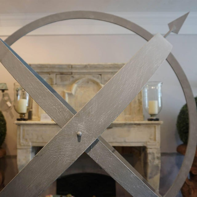 Simple yet stunning over sized armillary sphere pierced with an arrow, mounted upon a three foot scrolled base, which can...