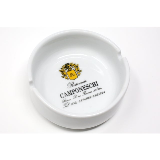A vintage white ceramic ashtray printed with the logo of Ristorante Camponeschi, located on Farnese Square in Rome, Italy....