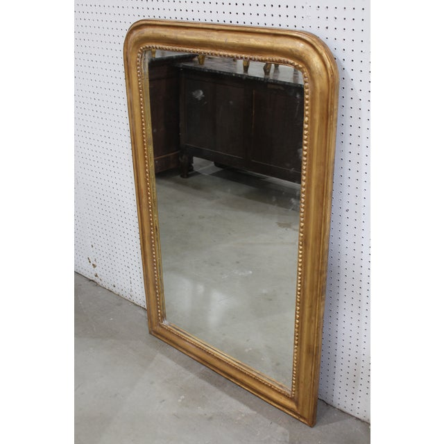 French gilt carved wood and gesso etched braided cross hatching wall mirror with flanking rounded corners, red lacquer and...