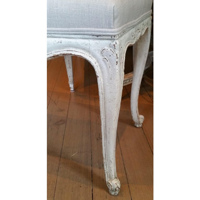 Beautifully hand carved bench; freshy upholstered in gray.