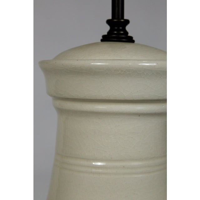 This beautiful, urn shaped lamp with an ivory, crackle glaze is accented with ribbed stripe details. It has an adjustable...