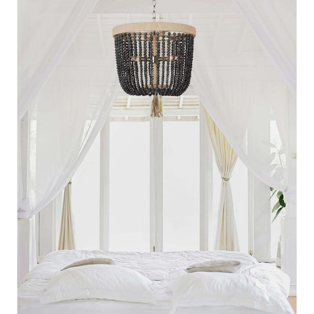 Round denim blue beads form the dynamic shade of the Milos chandelier, whose frame is wrapped with natural rope and...