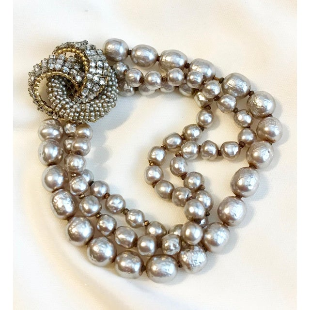 Circa 1950s Miriam Haskell triple strand, soft-white baroque faux-pearl bracelet with an ornate jeweled clasp. The clasp...