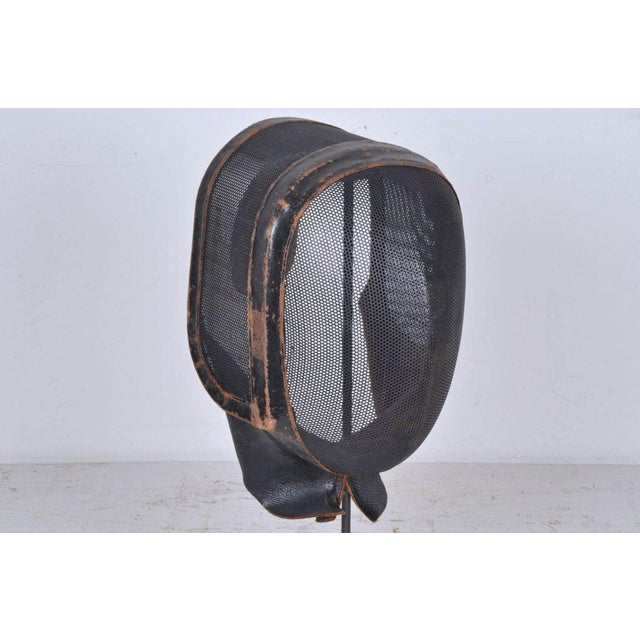 Originally used as a real fencing mask. It has been repurposed as an interesting display piece by adding a custom stand....