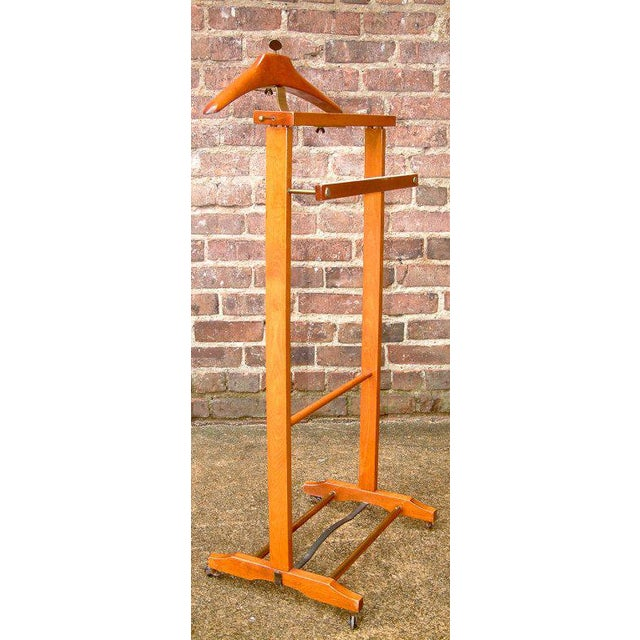 Italy Circa 1950 A nice variation on the classic valet with various adjustable parts. The stained beech & brass valet on...