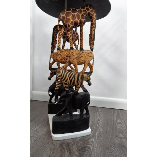 Unusual Safari style accent side table. The supports / Legs of the table are made of carved African animals stacked....