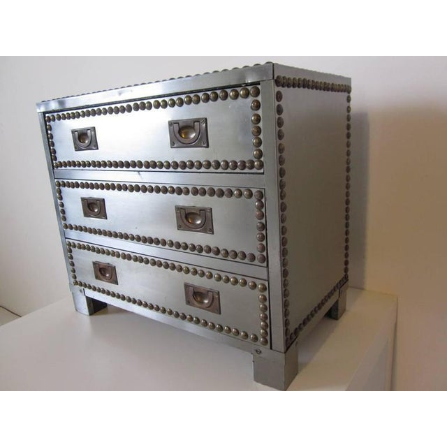 A three-drawer jewelry box covered in stainless steel with brass toned Studs and brass inset pulls with wooden internal...