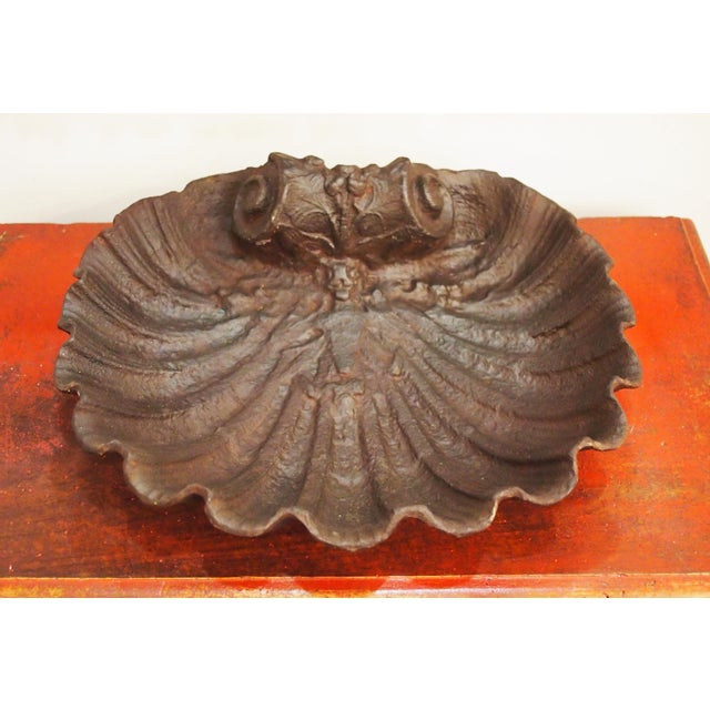 An iron shell form basin, with a scrolled top embellished with flowers, the shell ribs deeply molded. Delightful as a...