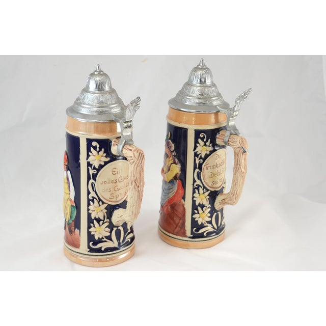 Celebrate OKTOBERFEST with a pair of hand painted embossed authentic German beer tankard steins with tavern scenes and a...