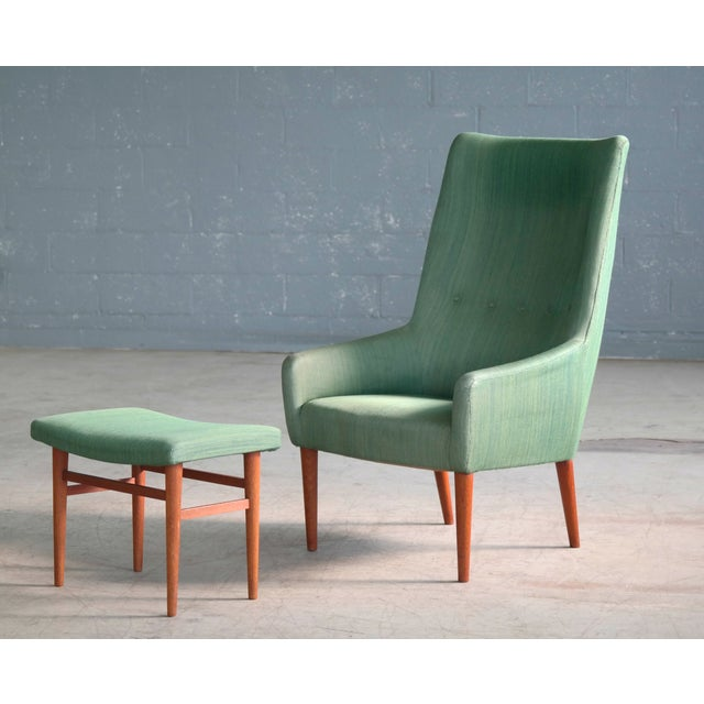 Superbly elegant high back easy chair with matching footstool made by Master Furniture and Cabinet Maker Jacob Kjaer. We...