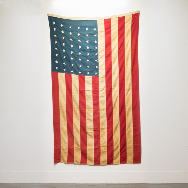 ABOUT This is an original fabric large American flag with 48 stars and metal grommets to hang it. The flag has retained...