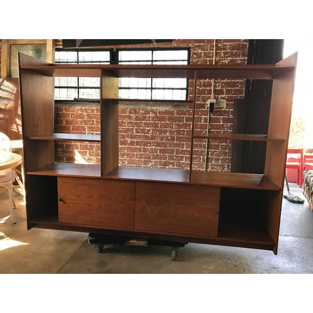 Teak Danish bookshelf features multiple sections and two sliding doors at bottom. There are brown leather pull on the...