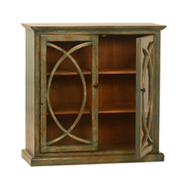 Deco style side cabinet with glass doors and distressed muted green paint finish. Includes metal pulls and two shelves....