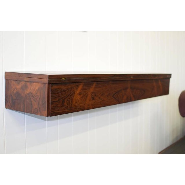 "Flip Top Wall Mounted Rosewood Console by Arne Hovmand-Olsen. Measures 12""deep X 60 long X 7.38 high. Measures 19.75 when..."