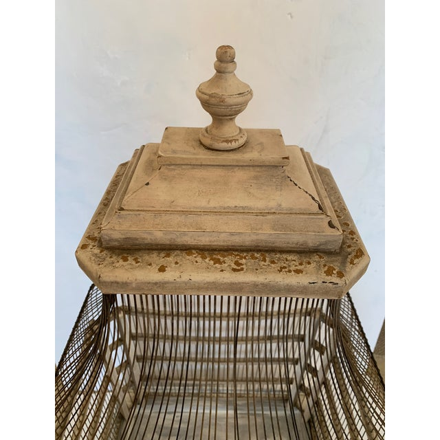 A large functional country style vintage birdcage having weathered grey painted natural wood and wire construction, door...