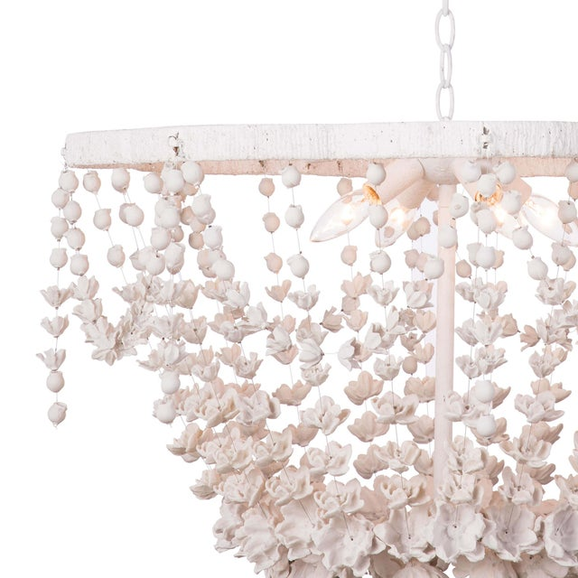 Hundreds of delicate white blooms are strung together on the quatrefoil-shaped frame of the Vanessa basin chandelier,...