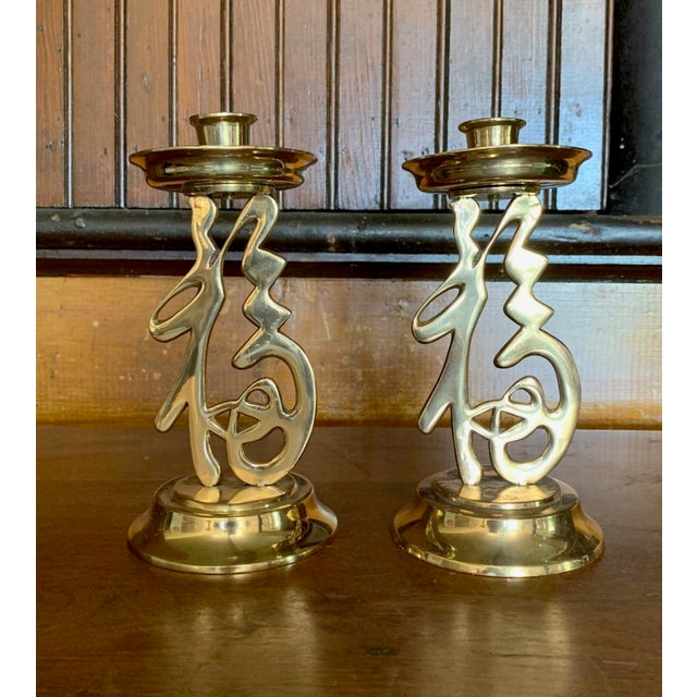Offering a pair of figural Asian candlesticks crafted out of brass. Tall, ideal for creating an eye catching centerpiece....