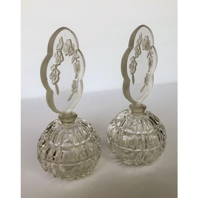 Elegant pair of Irice optic glass vanity dresser perfume bottles with crystal cut intaglio rose blossom stoppers. Both are...
