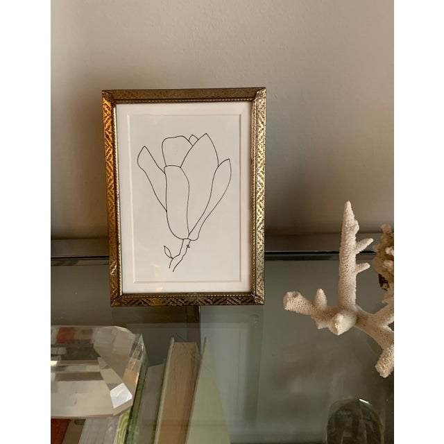 This original pen drawing of a blossom is framed in a vintage gold metal frame. The frame can stand or be hung on the wall.
