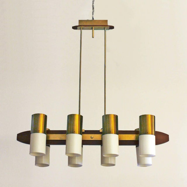 Chandelier with eight lights, solid teak, polished brass and plexiglass lampshades. Italy, circa 1960. Lampshades height:...