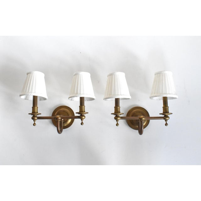 A pair of vintage, mid-century, brass double wall sconces, with round back plates and turned details paired with straight...