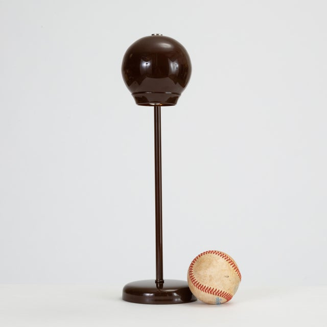 A delicate desk or table lamp with a glossy brown enamel finish provides concentrated task lighting via a rounded ball...