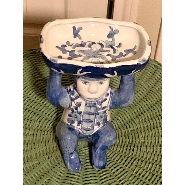 Delightful blue and white seated monkey holding a decorated dish on his head. This is a great sized. ceramic figure that...