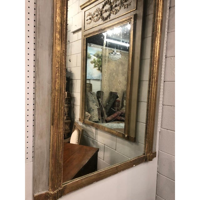 19th century French Louis XVI raised gilt mirror. Painted with foliate and garland crest.
