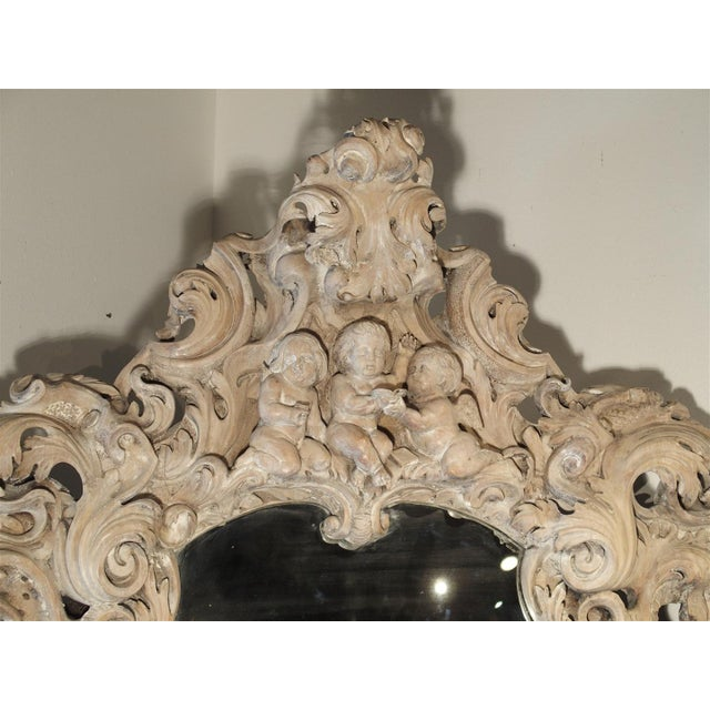 This very large, highly carved, wooden oval mirror is absolutely stunning. It's large motifs and dramatic flourishes to...