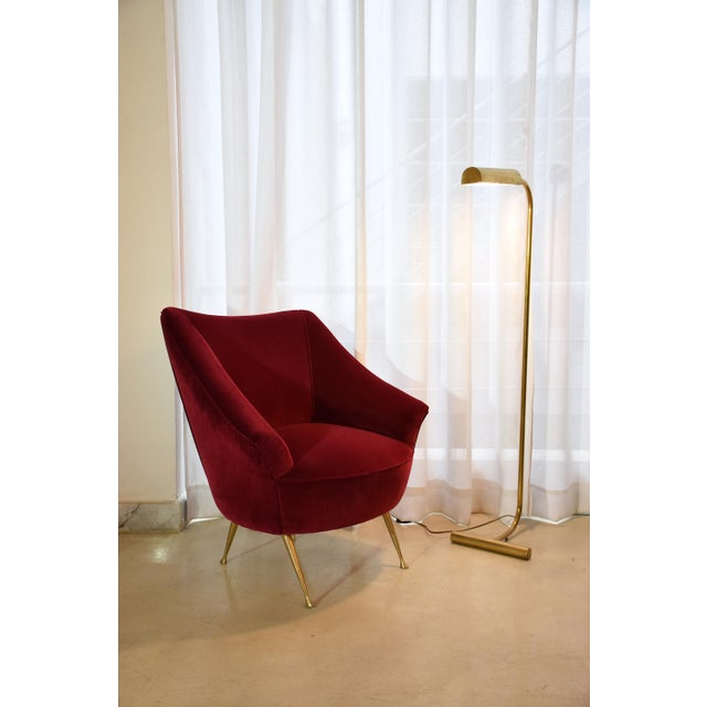 An Italian 20th century vintage brass-legged, curved armchair fully restored with one of the highest quality French...