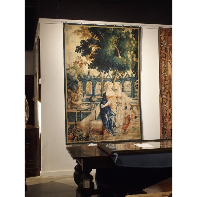 This vibrant antique tapestry fragment is a depiction of two women in a park setting adjacent to a chateau and its...