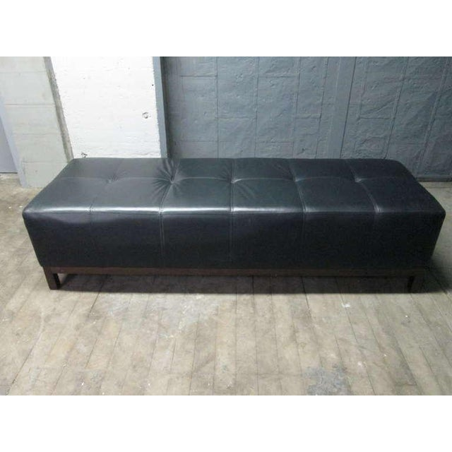 Black leather tufted bench with wood base.