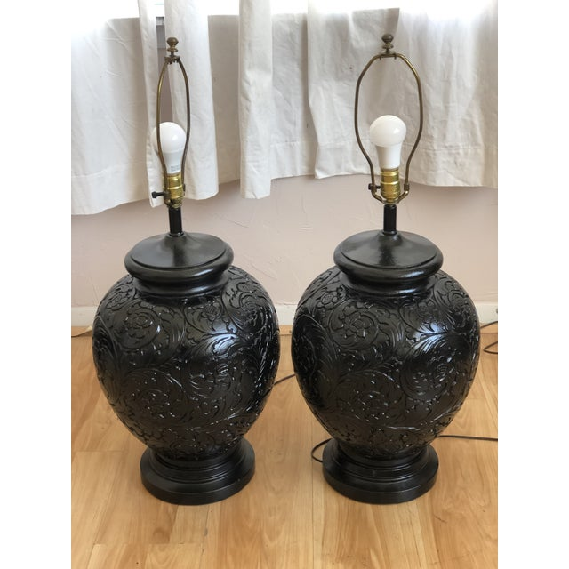 This pair of table lamps are absolutely chic and unusual with a carved, base relief design, finished in gloss black and of...