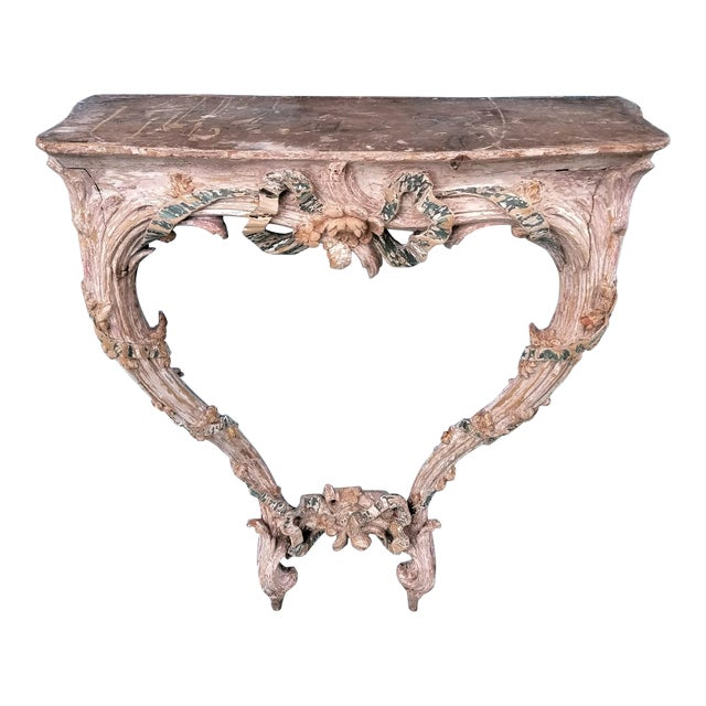 This unique console is intricately carved with flowers and ribbons. Each angle offers another view of masterful...