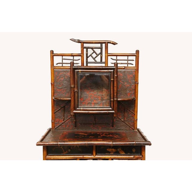 A fine aesthetic movement bamboo and lacquer etagere or dressing cabinet having an openwork pediment above a beveled glass...