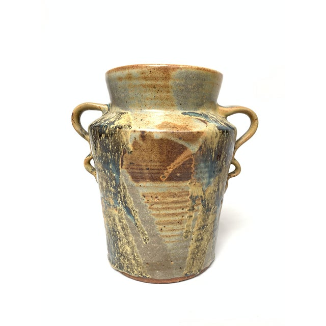 This hand-thrown amphora vase features a wide mouth and two applied handles and layers of earthy glazes in pale gray,...