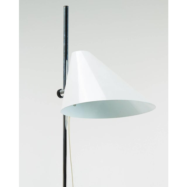 A floor lamp designed by Hans-Agne Jakobsson, Sweden, circa 1970. White metal adjustable height shade on polished chrome...